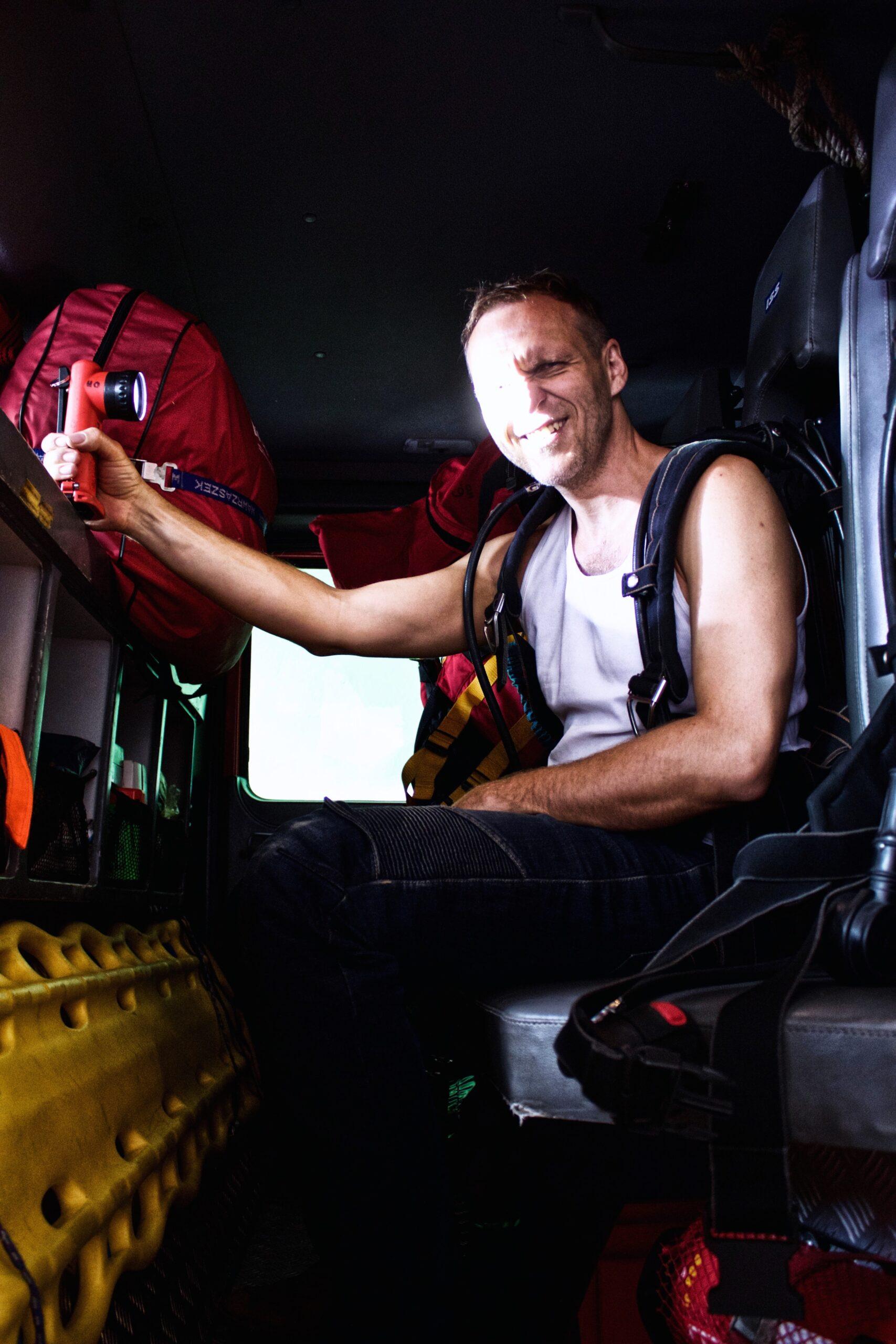 Hasič Honzo sa nechcel fotiť, tak musel zaskočiť redaktor Honzo Strmisko. V kabíne sú integrované dýchacie prístroje. Oblečiete si to priamo za jazdy. Stlačíte gombík, natiahnete si to ako batoh na chrbát a on potom vyskočí. Je v tom vzduchová fľaša.